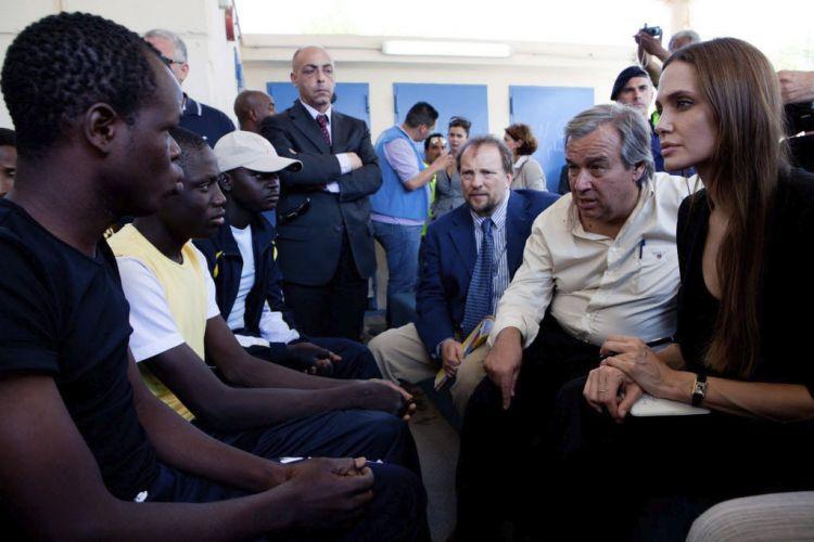 Em foto divulgada esta segunda-feira (20/6), Angelina Jolie e o alto comissário da ONU Antonio Guterres (ao lado da atriz) conversam, no domingo (19), com refugiados da guerra na Líbia em centro de imigração na ilha de Lampedusa, na Itália. Lampedusa é o ponto mais próximo do norte da África. Na última sexta-feira, Jolie visitou campo de refugiados sírios na Turquia