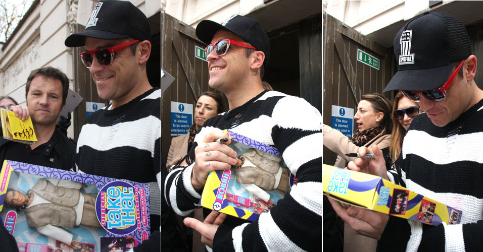 O cantor Robbie Willians autografa sua versão em boneco do grupo Take That na saída de estúdio em Londres (25/11). A banda se reuniu para gravar um novo álbum