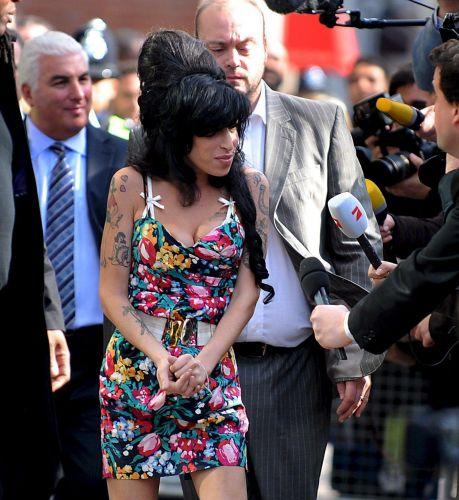 Amy Winehouse, bem disposta, responde aos jornalistas que a questionam sobre como a cantora está se sentindo: