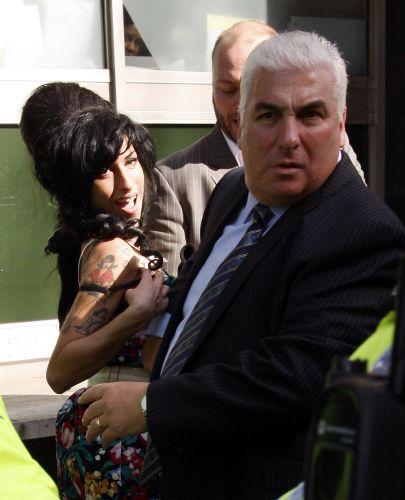 Simpática, Amy é acomapanhada por seu pai, Mitch Winehouse, à audiência sobre agressão em Westminster, Inglaterra (17/3/09)
