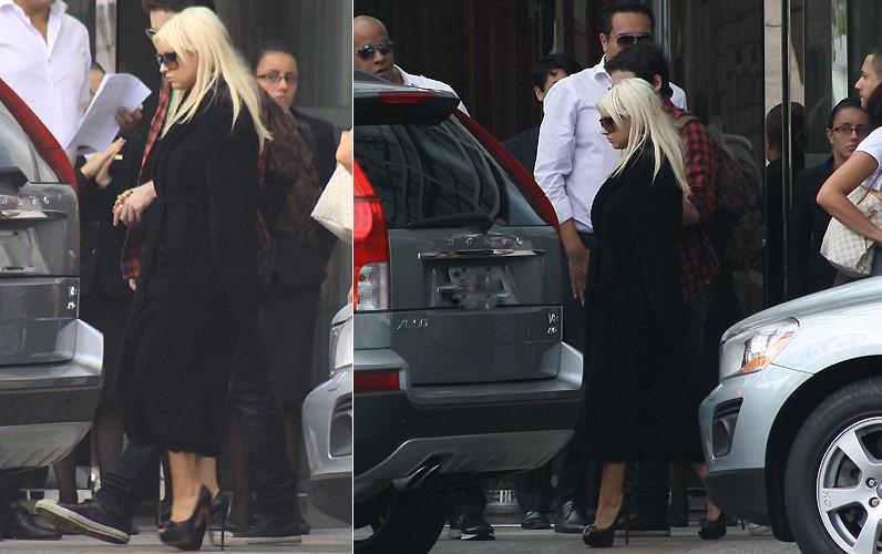 Apesar do forte calor, Christina Aguilera é fotografada com um trench coach preto, na saindo de seu hotel em São Paulo (1/2/2011)