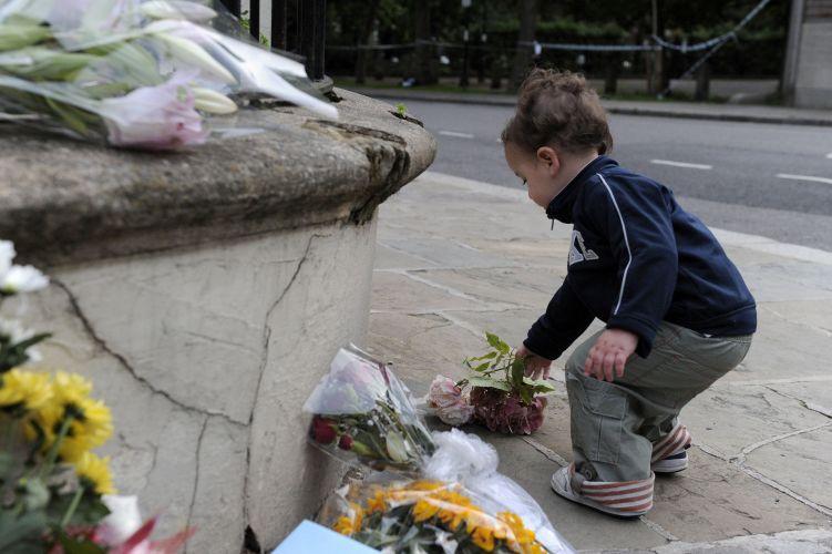 Garoto deixa flores em frente à casa de Amy Winehouse, neste sábado (23/7/11)