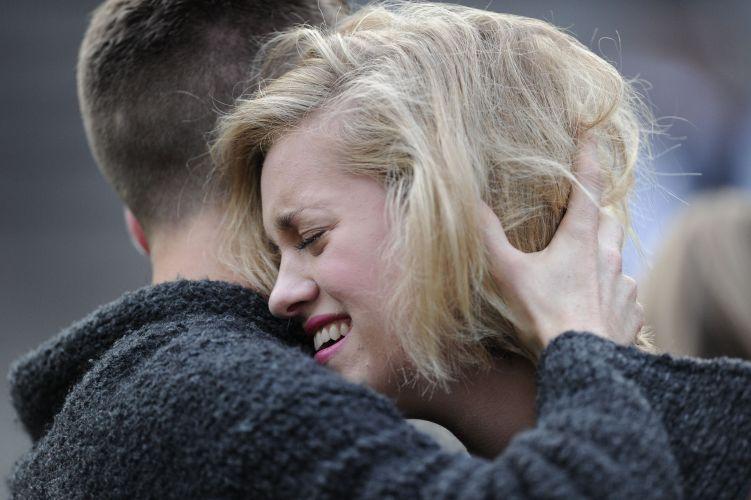 Fã chora e é consolada em frente à porta da casa de Amy Winehouse, que foi encontrada morta neste sábado (23/7/11)