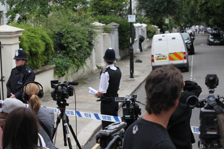Jornalistas se posicionam atrás de cordão de isolamento próximo à casa de Amy Winehouse, que foi encontrada morta neste sábado (23/7/11)