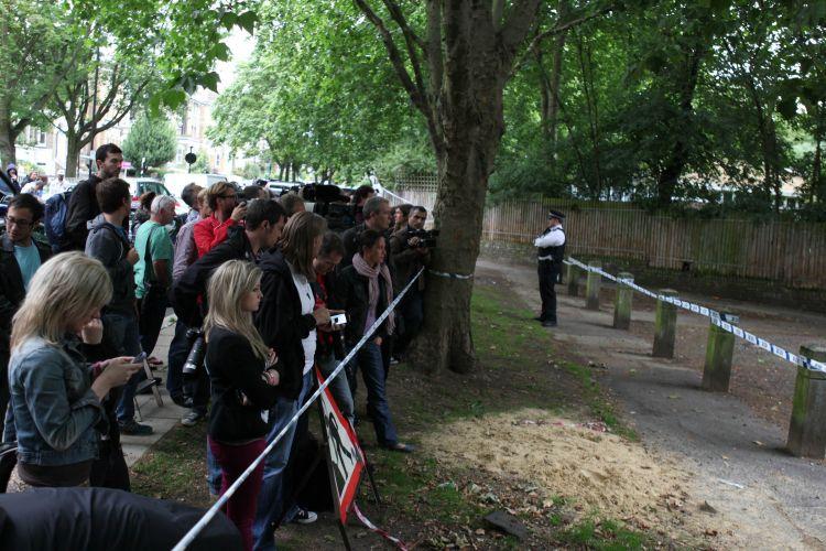 Jornalistas e fãs se aglomeram atrás de cordão de isolamento, próximo à casa de Amy Winehouse, que foi encontrada morta neste sábado, em Londres (23/7/11)