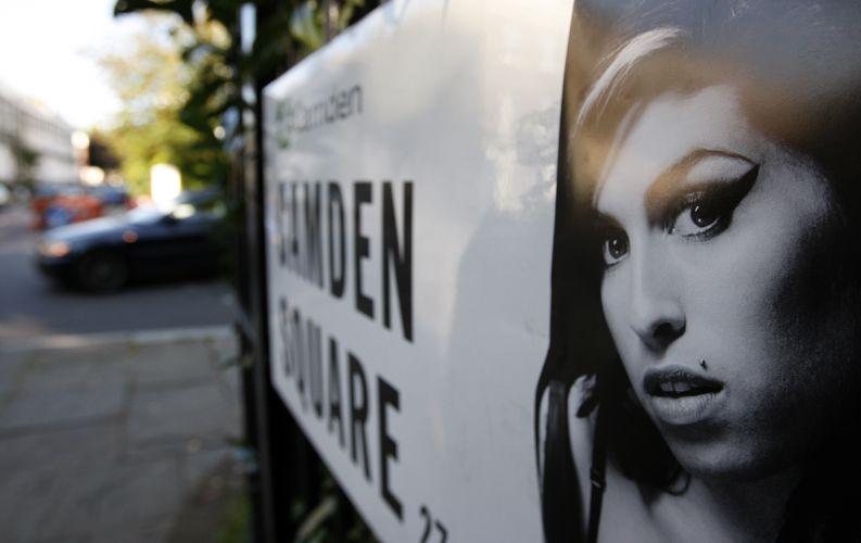 Uma foto de Amy Winehouse é colocada na placa de uma rua próxima à casa onde a cantora morava em Camden Square, em Londres (24/07/2011)