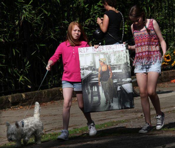 Garotas carregam pôster de Amy Winehouse próximo à casa onde a cantora morava em Camden, em Londres (24/07/2011)