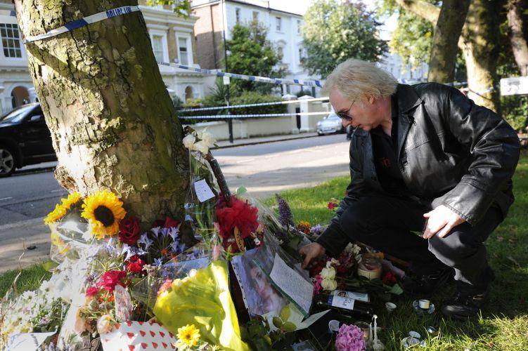 Um homem deixa flores em área para homenagens à Amy Winehouse em frente à casa onde a cantora morava em Camden, em Londres (24/07/2011)