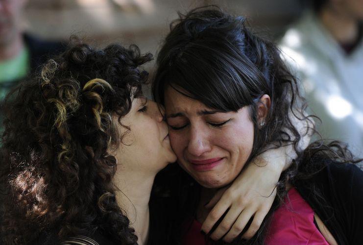 Uma mulher conforta a amiga em frente à casa onde Amy Winehouse morava em Camden, em Londres (24/07/2011)