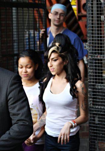 Sob o olhar de um médico, Amy Winehouse sai de uma clínica em Londres, acompanhada da afilhada Dionne Bromfield, de 13 anos (10/10/2009). No mesmo dia, as duas participaram do programa