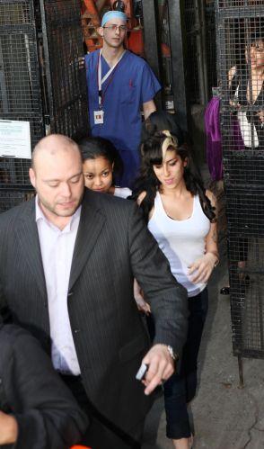 Acompanhada de uma equipe e da afilhada Dionne Bromfield (esq.), Amy Winehouse deixa uma clínica de Londres sob o olhar de um médico (ao fundo, de azul). A cantora participou do programa
