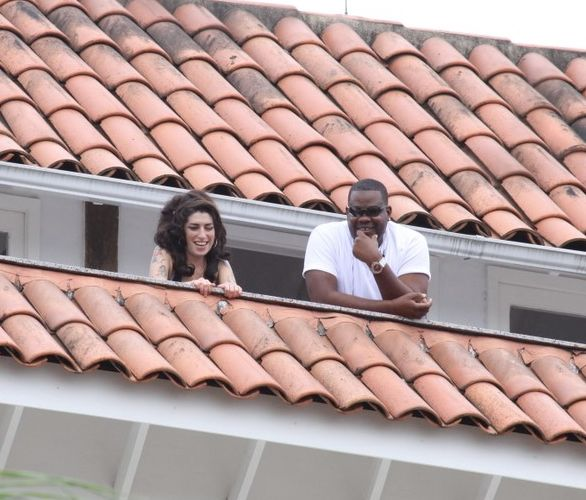 Com seu segurança particular, Amy Winehouse aparece na sacada do hotel em que está hospedada em Santa Teresa, na região central do Rio de Janeiro (5/1/11)