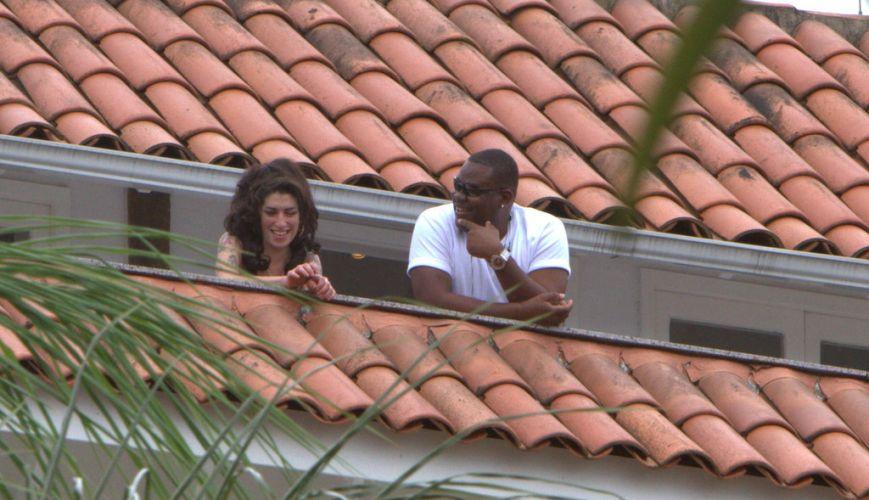 Amy Winehouse conversa com seu segurança particular na sacada do hotel em que está hospedada em Santa Teresa, na região central do Rio de Janeiro (5/1/11)
