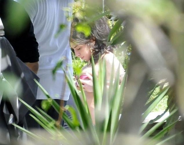 Amy Winehouse ajeita a parte de cima do biquíni. A cantora foi flagrada na beira da piscina do hotel em que está hospedada, em Santa Teresa, no Rio (6/1/2011)
