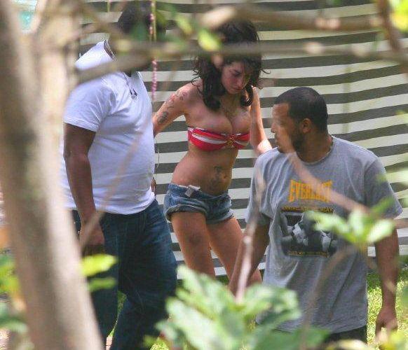 Ao deixar a piscina do hotel em que está hospedada no Rio, Amy Winehouse exibe uma mancha roxa na perna (7/1/2011)