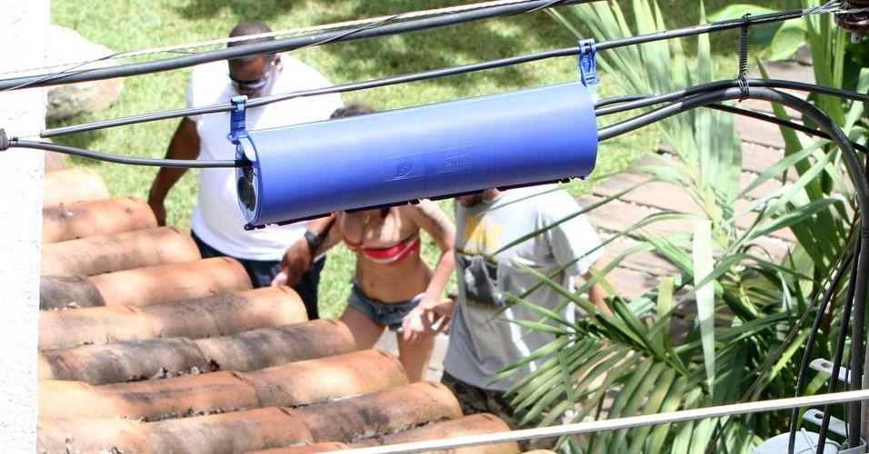 Amparada por membros de sua equipe, Amy Winehouse deixa a piscina do hotel em Santa Teresa, no Rio de Janeiro (7/1/2011)