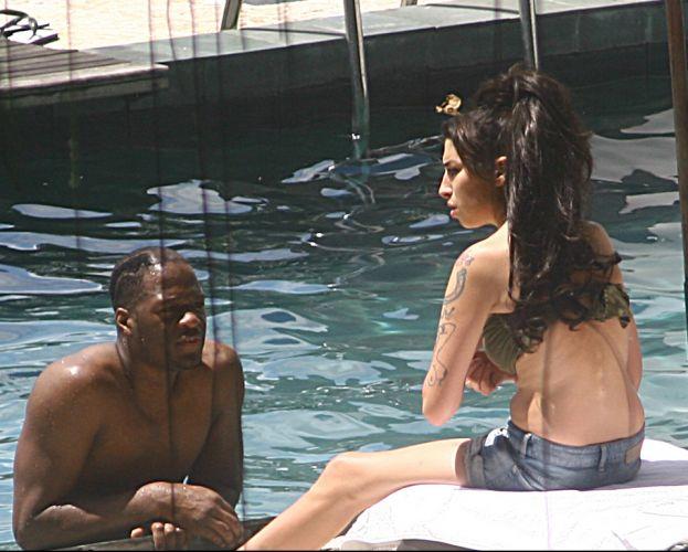 Com seu inseparável short jeans, a cantora Amy Winehouse conversa com membro de sua equipe na beira da piscina do hotel Santa Teresa, no Rio de Janeiro (11/1/2011). Na segunda-feira (10), a cantora fez seu primeiro show na Cidade Maravilhosa. Veja os famosos no show O segundo acontece nesta terça (11)