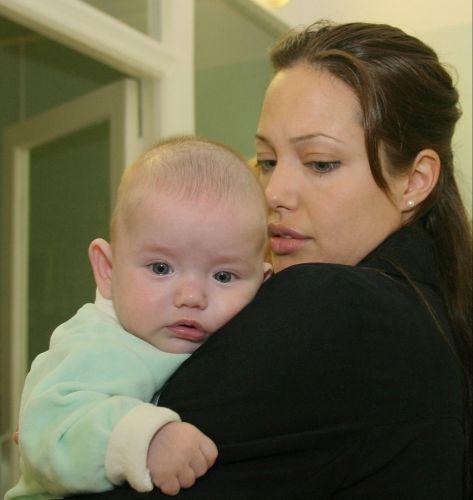Angelina Jolie segura um bebê durante visita ao hospital infantil de Morozov, em Moscou. A atriz e embaixadora da ONU doou 20 mil dólares ao hospital (21/8/03)