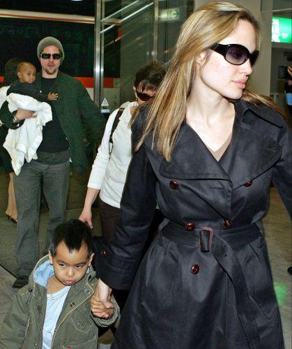 Com o cabelo mais curto e em tons de loiro, Jolie é fotografada com Brad Pitt e os filhos Maddox e Zahara no aeroporto de Tóquio (27/11/05)