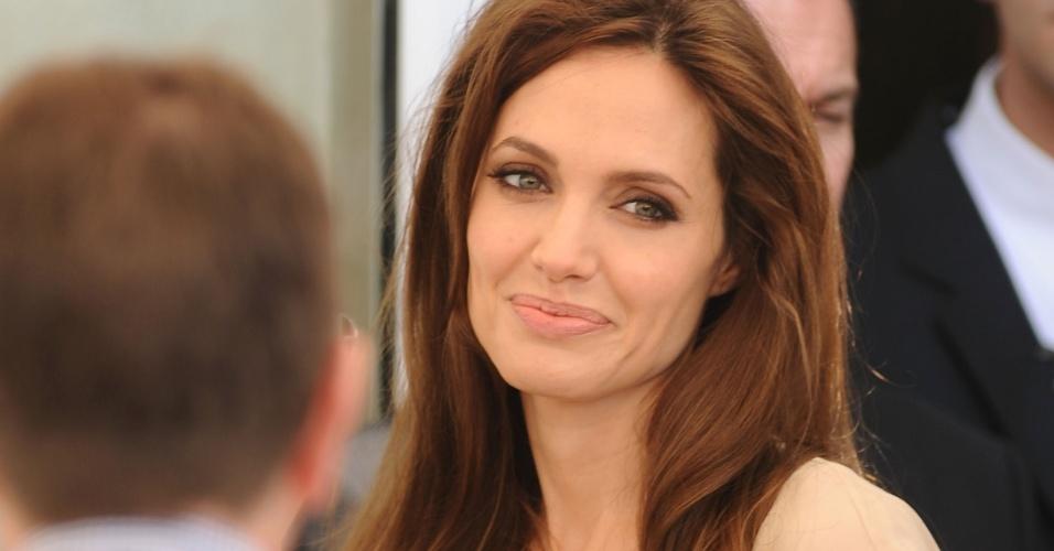 Angelina Jolie sorri enquanto aguarda o início da sessão de fotos de divulgação do filme