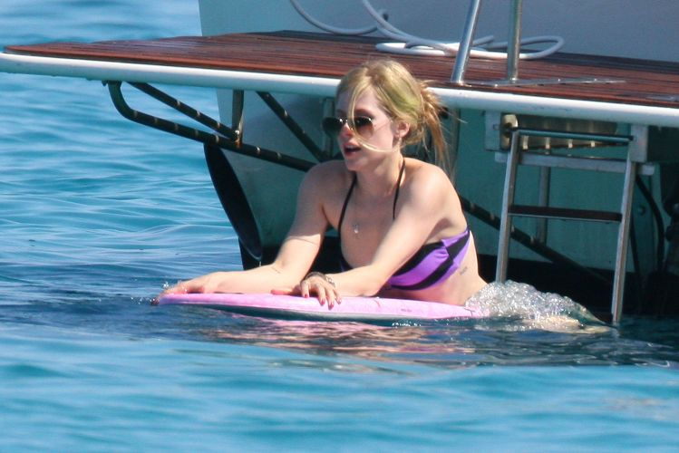 Ao lado de amigas, Avril Lavigne curte dias de sol em St. Tropez, na França e aproveita para surfar(26/6/11)