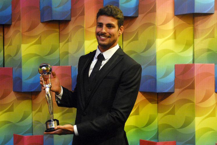 Cauã Reymond posa com o prêmio de melhor ator coadjuvante no