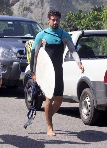 O ator Cauã Reymond anda descalço pela rua ao lado da Prainha antes de surfar (28/8/11)