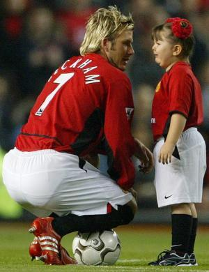 Ainda no Manchester, Beckham tenta acalmar a pequena garota que chorava (07/10/02)