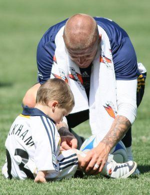 Beckham cuida de um dos seus filhos, após jogo de futebol familiar (22/3/08)