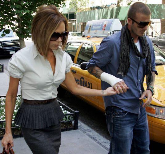 David Beckham caminha ao lado de sua mulher, Victoria, com um curativo na mão direita, ao deixar restaurante em Nova York (2/6/08)
