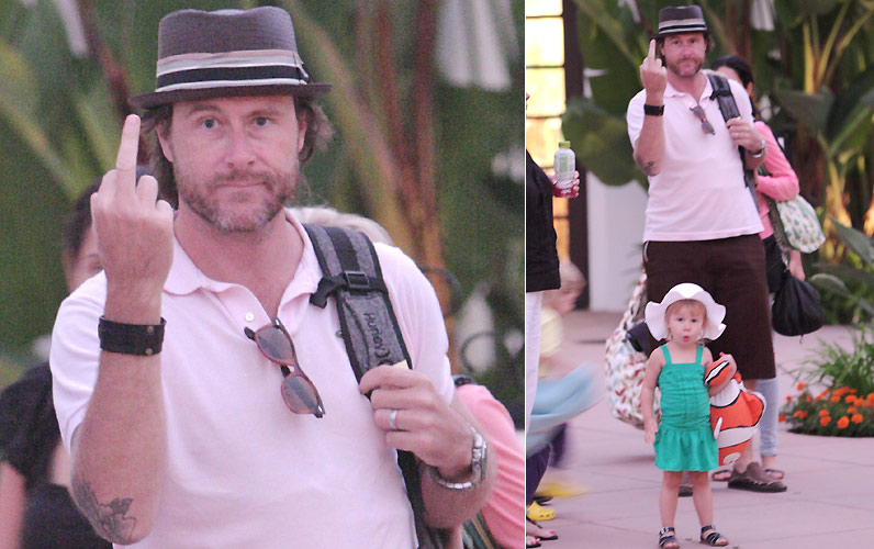 O marido da atriz Tori Spelling, o também ator Dean McDermott, mostra o dedo médio para os fotógrafos durante passeio ao lado da mulher e dos filhos Liam e Stella (de vestido verde), em Loyola, na Califórnia (29/7/2010)