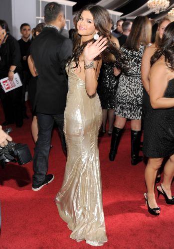 A atriz e cantora Selena Gomez acena para o fotógrafo no tapete vermelho do Grammy 2011 (13/2/2011)