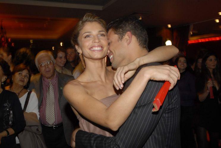 Grazi Massafera recebe o abraço do namorado Cauã Reymond na festa de lançamento da novela