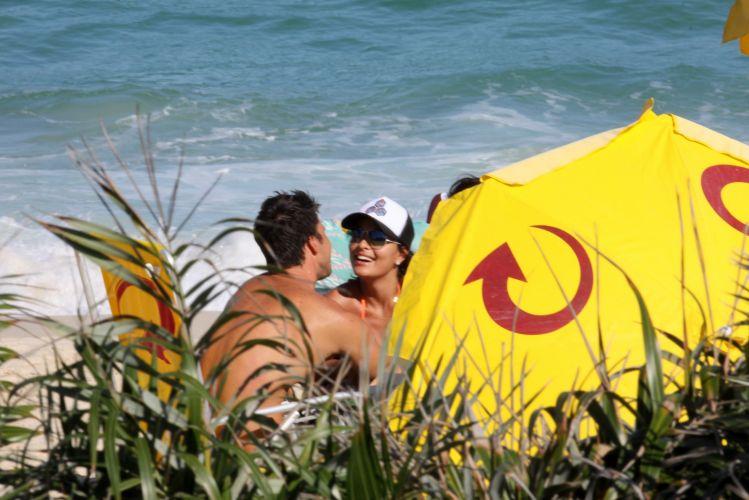 Juliana Paes e o marido, Carlos Eduardo Baptista, aproveitaram o feriado e o sol carioca para descansar na praia. O casal trocou beijos apaixonados nas areias da Barra da Tijuca, Rio de Janeiro (1/5/2010)