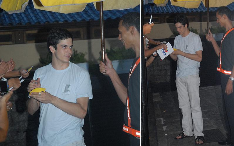O ator Mateus Solano conversa com um segurança, que o protege da chuva, enquanto atende fãs na comemoração do aniversário de Taís Araújo, no Rio de Janeiro (30/11/2009)