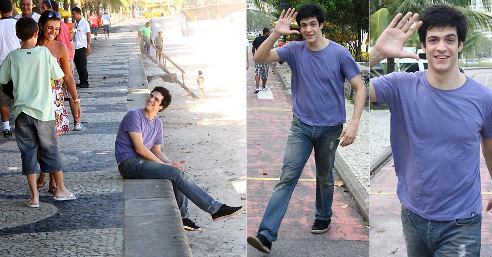 O ator Mateus Solano sorri para fãs e acena para paparazzo ao ser fotografado no intervalo de uma gravação de