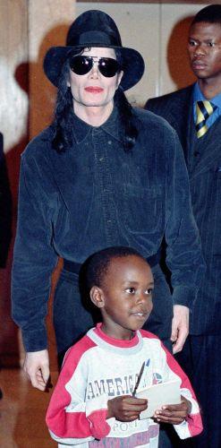 O cantor Michael Jackson aparece ao lado do menino Anesuishe Gwini após dar um autógrafo para ele, em Harare, Zimbábue (17/11/98)