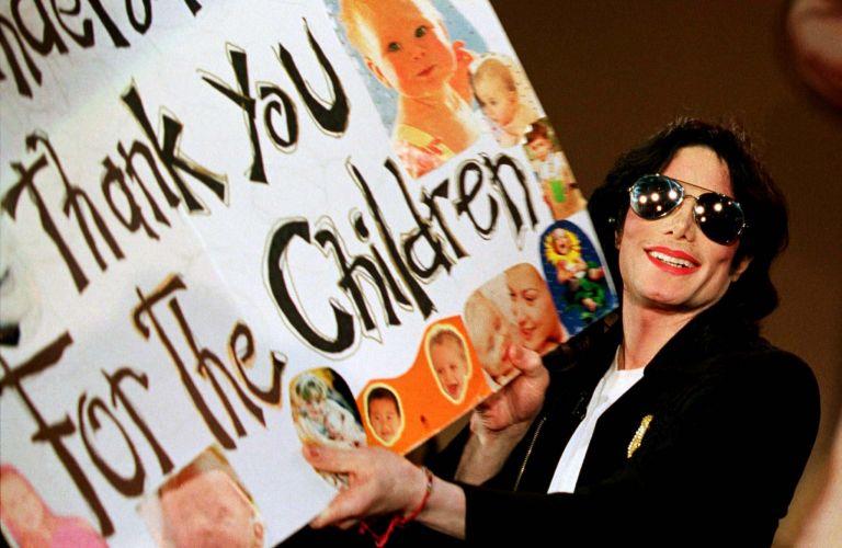 Michael Jackson exibe pôster que ganhou de fãs, após aparecer em um programa de televisão na Alemanha (20/3/99)