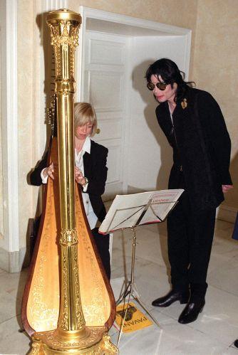 O cantor Michael Jackson observa o menino Rhian Willi tocar harpa na loja Harrods, em Londres (10/4/99)