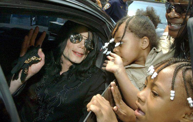 Dentro de sua limusine, Michael Jackson cumprimenta crianças nas ruas Nova York (6/7/02)