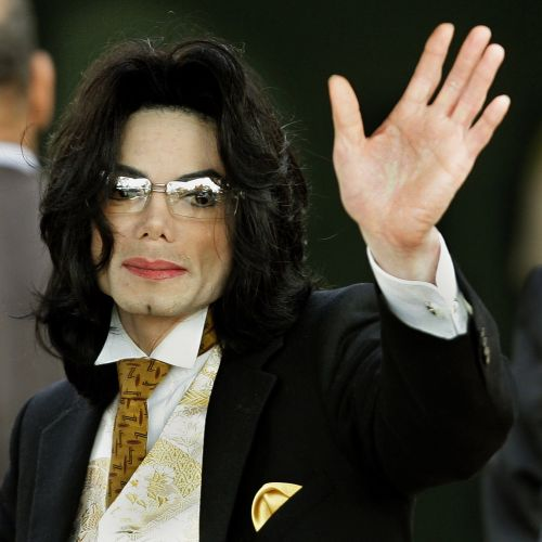 O cantor Michael Jackson acena aos fãs ao chegar no tribunal de Santa Barbara para o seu julgamento contra a acusação de abuso sexual (3/6/05)