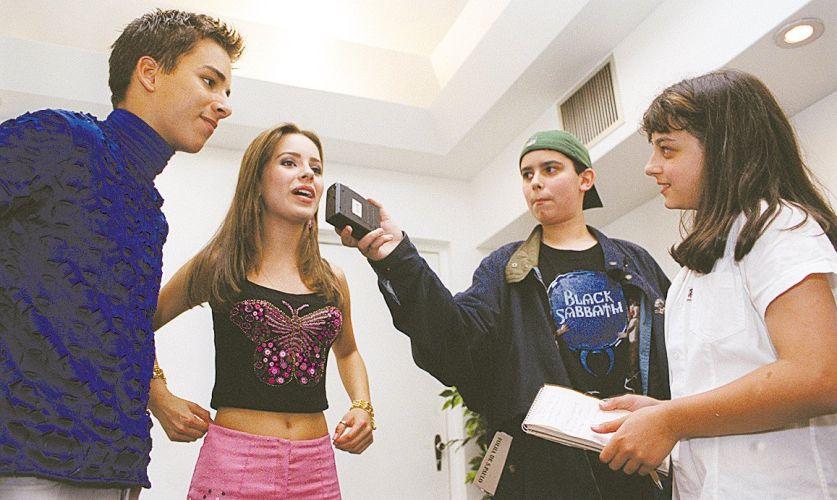 Sandy, acompanhada de Junior (esq.), dá entrevista na festa de apresentação dos vencedores do prêmio Kids Choice 2000, da Nickelodeon, a repórteres da Folhinha, do jornal Folha de S.Paulo (7/10/2000)