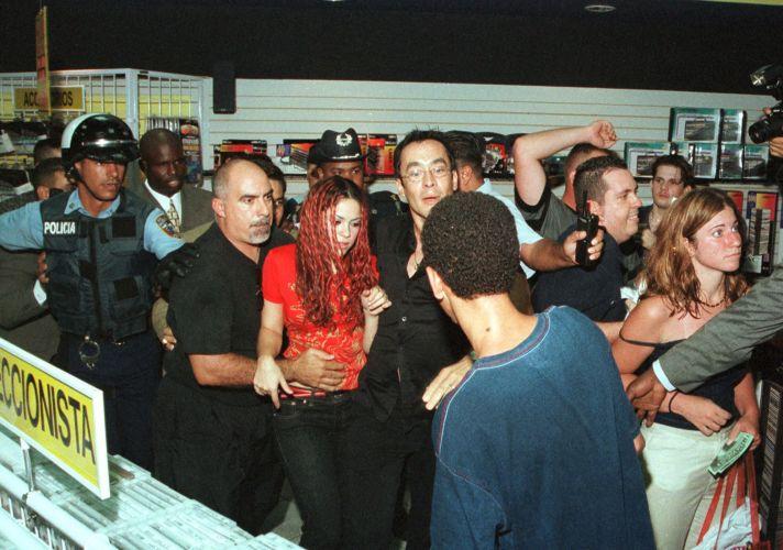 Shakira recebe ajuda de seguranças e policiais em loja de discos em Porto Rico (1/7/1999). Cerca de mil fãs foram até o local ver a artista, que fez uma tarde de autógrafos