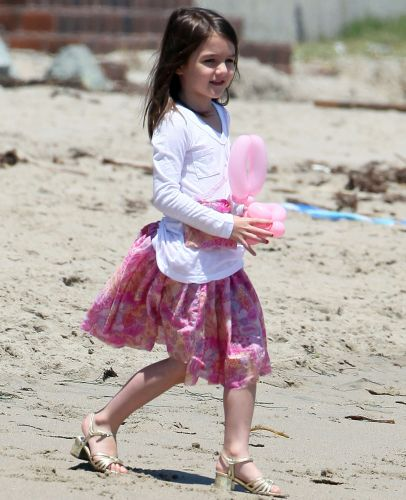 Suri Cruise, de cinco anos, usa sandália de salto dourado, durante brincadeira na praia com a mãe Katie Holmes, em Malibu (30/5/2011)