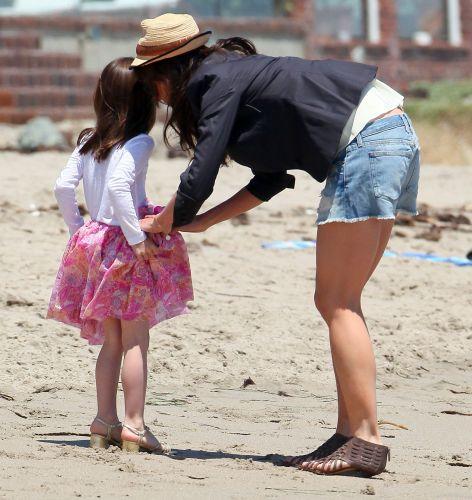 Katie Holmes arruma a saia da filha Suri durante brincadeira na praia, em Malibu (30/5/2011). Detalhe para os saltos usados pelas duas