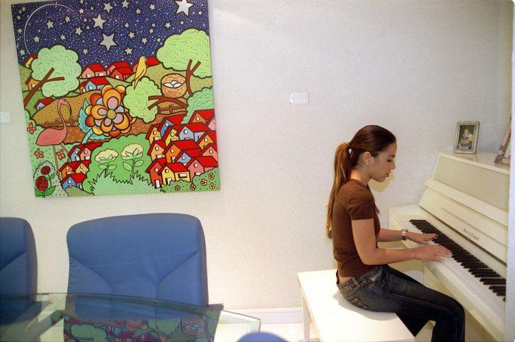 Wanessa Camargo toca piano no escritório da casa de seus pais. Em seu quinto disco,