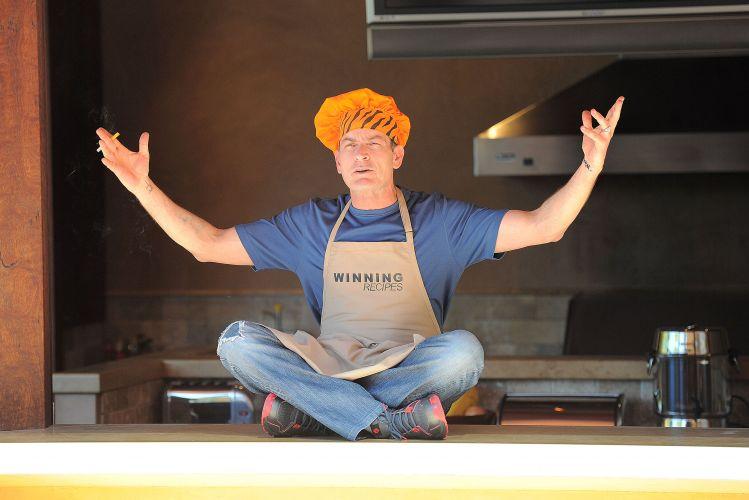 Vestido de chef de cozinha, o ator Charlie Sheen grava um vídeo para o site