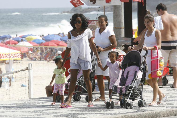 Com o auxílio de duas babás, Glória Maria passeia com as filhas no calçadão do Leblon, no Rio de Janeiro (2/4/2011)