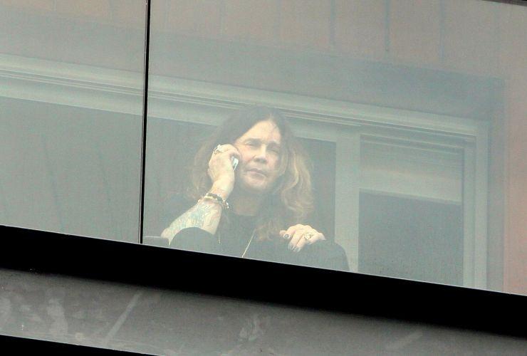 Depois de cantar em São Paulo no sábado (2), Ozzy Osbourne aparece na varanda do hotel onde está hospedado ao celular (3/4/2011)