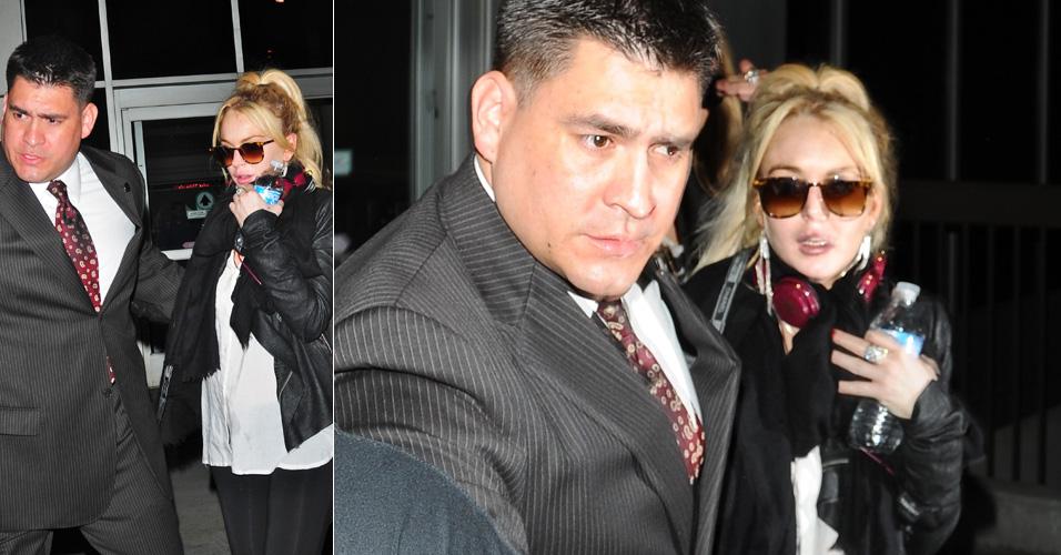Lindsay Lohan desembarca em aeroporto na Califórnia e é auxiliada por Alberto Alvarez, ex-guarda-costas de Michael Jackson (09/04/2011)